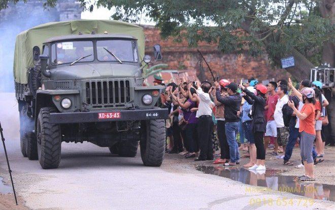 Hình ảnh người dân đứng hai bên đường vãy tay tiễn đưa 13 liệt sĩ, cán bộ